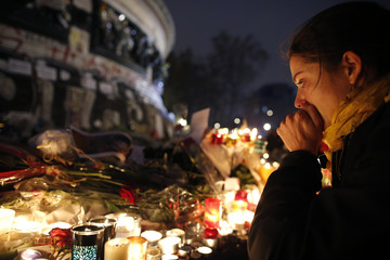 A woman weeps as she kneels near bouquets of flowers and burning candles at the Place de la Republique in Paris