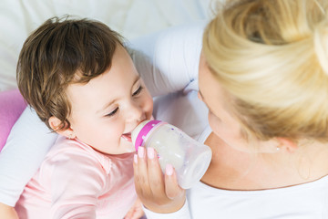 Baby little girl drinking a milk from bottle in the mom's arms.Shallow doff, high angle view