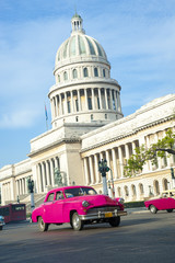 Foto op Canvas Havana Brightly colored classic American cars serving as taxis pass on the main street in front of the Capitolio building in Central Havana, Cuba