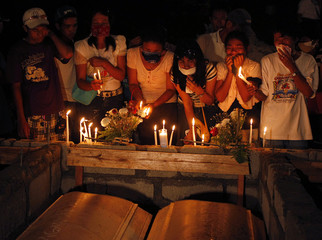 Relatives grieve during a mass burial for Typhoon Washi victims in Iligan city, southern Philippines