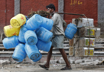 A man carries empty oil containers to a recyclable factory in Kolkata
