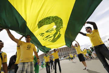 Brazil fans carry  a picture of soccer legend Pele before the 2014 World Cup Group A soccer match between Cameroon and Brazil at the Brasilia national stadium