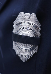 A mourning band is seen placed over a fire department badge as firefighters arrive for the calling hours for firefighters Chiapperini and Kaczowka in West Webster