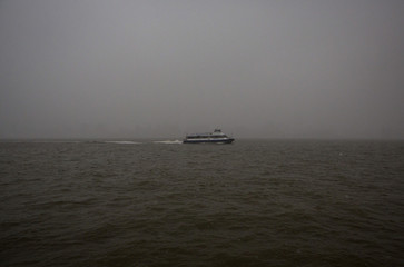 A ferry is seen on the Hudson River with the New York skyline obscured by fog from Hoboken, New Jersey