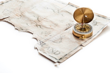 Close up to gold nautical compass on old vintage map with fake island of Pirates treasure