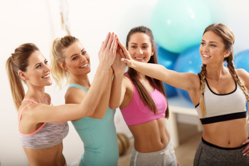 Foto op Plexiglas Dance School Young women group gicing high five at the gym after workout
