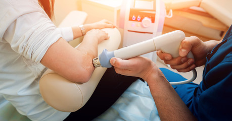 Shock wave therapy. The magnetic field, rehabilitation. Physiotherapist doctor performs surgery on a patient's elbow