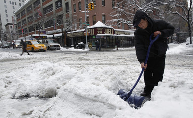 A worker shovels a path from the street to the sidewalk after heavy snowfall during a winter storm in New York