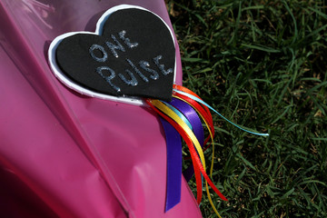 A tag on a bouquet of flowers is pictured as part of a makeshift memorial the day after a mass shooting at the Pulse gay nightclub in Orlando