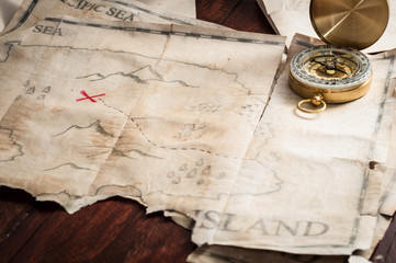 Top view to table with vintage map with abstract Island and nautical compass.