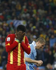Ghana's Gyan reacts after missing a penalty kick during extra time in the 2010 World Cup quarter-final soccer match against Uruguay at Soccer City stadium in Johannesburg