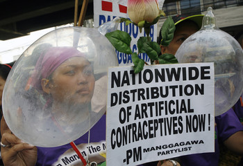 Reproductive health advocates display placards and inflate condoms during a protest in Manila