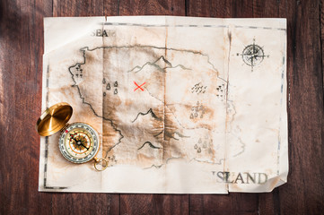 Fake vintage old broken map on wooden desk with compass. Pirates treasure map