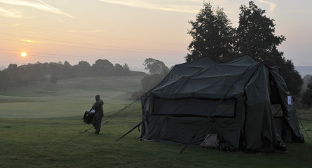 A soldier carries a case as the sun rises over the golf course at the Celtic Manor resort, near Newport