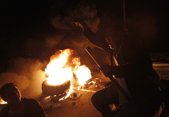 A Lebanese Sunni Muslim supporter of caretaker PM Hariri gestures in front of burning tires during a protest at Barja
