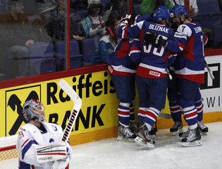 France's goalkeeper Huet reacts as Slovakia's players celebrate scoring during their 2012 IIHF men's ice hockey World Championship game in Helsinki