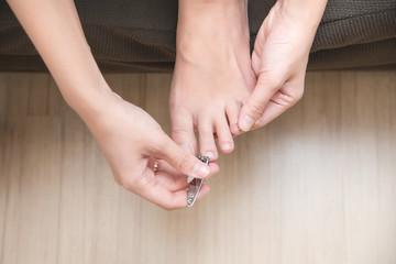 Closeup of woman cutting nails