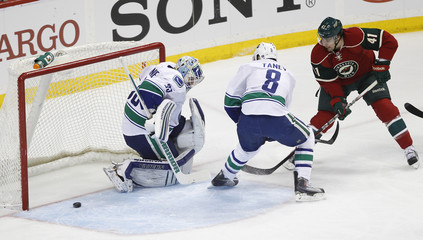 Vancouver Canucks goalie Schneider clears a shot by Minnesota Wild right wing Ortmeyer, as Canucks' Tanev defends, during their NHL hockey game in St. Paul