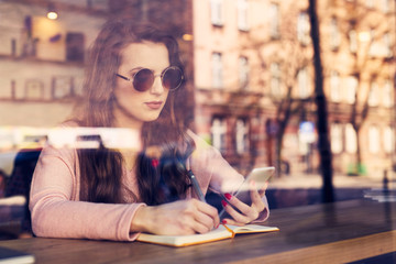 Woman at cafe using smartphone and taking notes