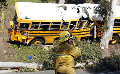 Fire-fighter walks past a school bus leaning against a eucalyptus tree after it veered off the road in Anaheim, southern California