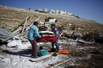 Palestinian boys carry their belongings after the Israeli army demolished their shanty, that their family lives in, near the Israeli West Bank settlement of Maale Adumim, near Jerusalem