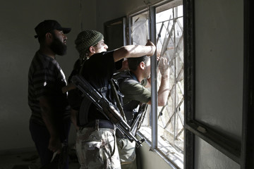 A Free Syrian Army fighter looks out of a building with binoculars as he stands with fellow fighters in Idlib