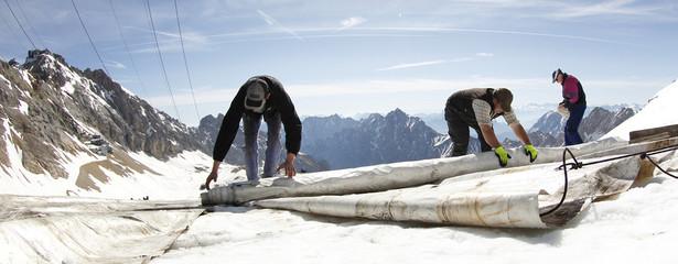 Worker install canvas covers on glacier ice on top of Germany's highest mountain Zugspitze near Garmisch-Partenkirchen