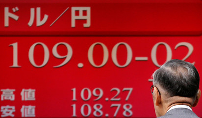 Man looks at an electronic board showing the exchange rates between the Japanese yen and the U.S. dollar outside a brokerage in Tokyo