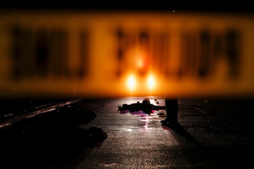 Bodies of two men are lit by a police car in Manila