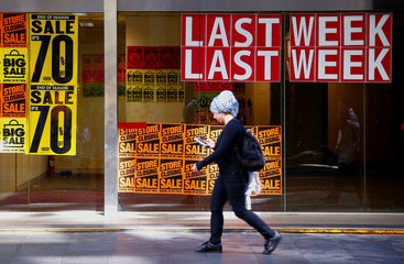 A pedestrian looks at her phone as she walks past a recently closed retail shop displaying sales posters in central Sydney, Australia