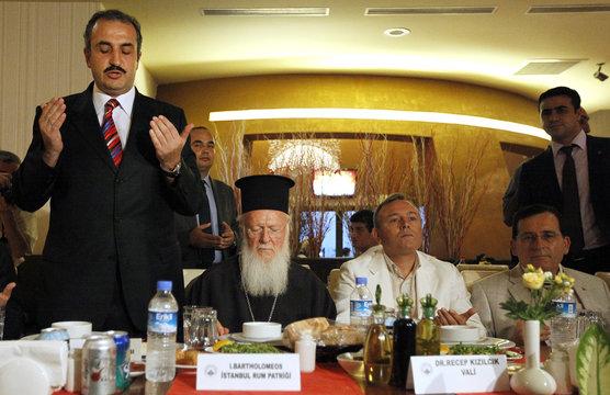 Ecumenical Orthodox Patriarch Bartholomew pauses as Trabzon's deputy Mufti Zeki Aksoy prays during an Iftar dinner in Turkey's Black Sea city of Trabzon