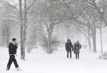 People walk through snow in a winter storm in Toronto