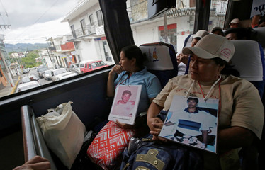 People from Central America, holding pictures of relatives who disappeared during their journeys through Mexico on their way to the U.S., sit on a bus after they took part in a march in Cordoba