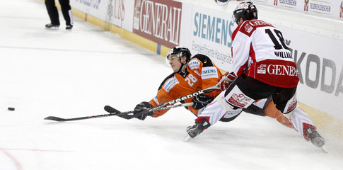 Team Canada's Williams is challenged by Bina of Grizzly Adams Wolfsburg during their game at the Spengler Cup ice hockey tournament in Davos