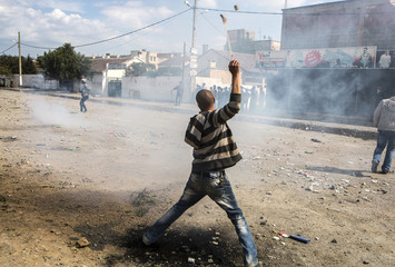 An anti-election protester throws stones during clashes with gendarmerie riot forces in Rafour, in Berber region