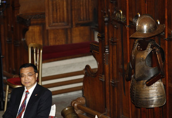 China's Vice Premier Li Keqiang sits next to a suit of armour during a state dinner at Edinburgh castle, Scotland