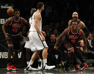 Chicago Bulls point guard Robinson and forward Boozer react after Robinson made a basket in front of Brooklyn Nets center Lopez for the lead late in the fourth quarter of their NBA basketball game in New York