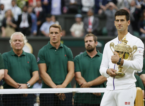 Novak Djokovic of Serbia holds the trophy as he waits to give a speech after winning his Men's Singles Final match against Roger Federer of Switzerland at the Wimbledon Tennis Championships in London