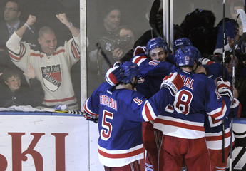 New York Rangers fans react as Rangers teammates mob Chris Kreider after he scored on the New Jersey Devils during the third period of Game 1 of the NHL Eastern Conference Finals hockey playoffs at Madison Square Garden in New York