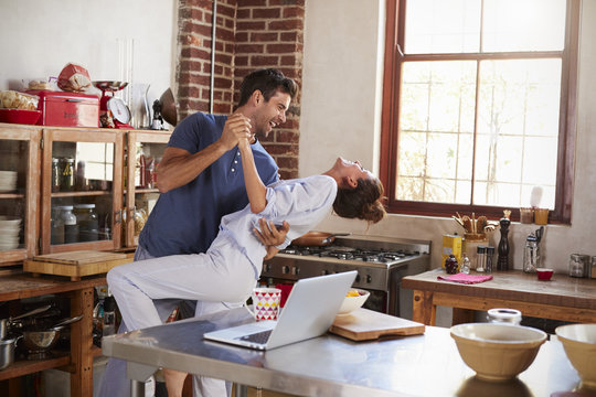 Happy Hispanic couple dancing in kitchen in the morning