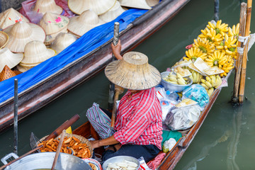 Local vendors selling goods at Damnoen Saduak Floating Market near Bangkok in Thailand, Damnoen Saduak is a very popular tourist attraction.