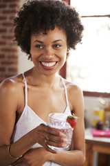 Happy mixed race woman holding smoothie, vertical