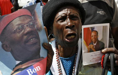 A woman shout slogans while attending a meeting for the return of Haiti's exiled former president Jean-Bertrand Aristide in Port-au-Prince