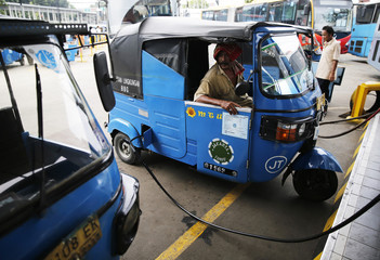 A driver sits inside his Bajaj auto rickshaw as he fills gas at a state-owned Pertamina gas station in Jakarta