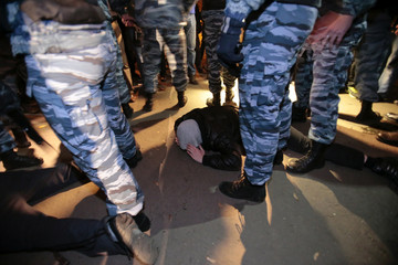 Russian police detain a man after a protest in the Biryulyovo district of Moscow