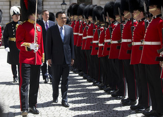 Chinese Premier Li Keqiang is followed by Britain's Prime Minister David Cameron as he inspects a Guard of Honour at the Treasury building in London