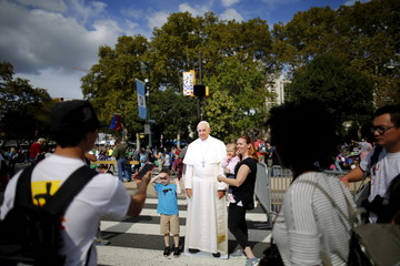 People pose for a picture with a cardboard cutout of Pope Francis as they wait for the pope's arrival at the Festival of Families rally along Benjamin Franklin Parkway in Philadelphia