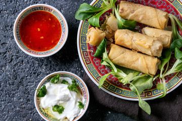 Fried spring rolls with red and white sauces, served in traditional china plate with fresh green salad over black texture background. Flat lay, space. Asian food