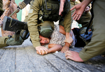 Israeli soldiers detain a Palestinian during a searching raid by Israeli troops, in the West Bank city of Hebron