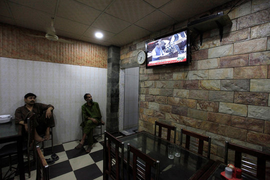 Men watch a TV screen showing live broadcast of Pakistani Prime Minister Nawaz Sharif giving a speech during a Parliament session, at a restaurant in Islamabad